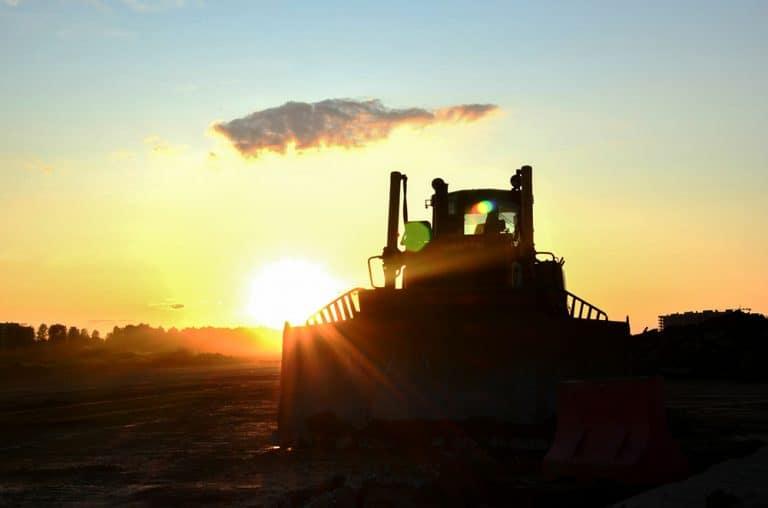 Front-end loader at sunset revitalizing surplus property on
