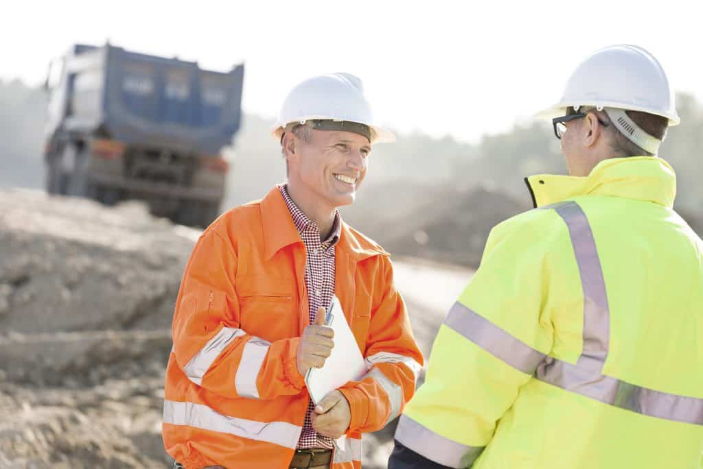 Manager on brownfield sites talking with colleague